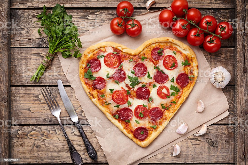Heart shaped pizza for Valentines day with pepperoni, mozzarella, tomatoes stock photo