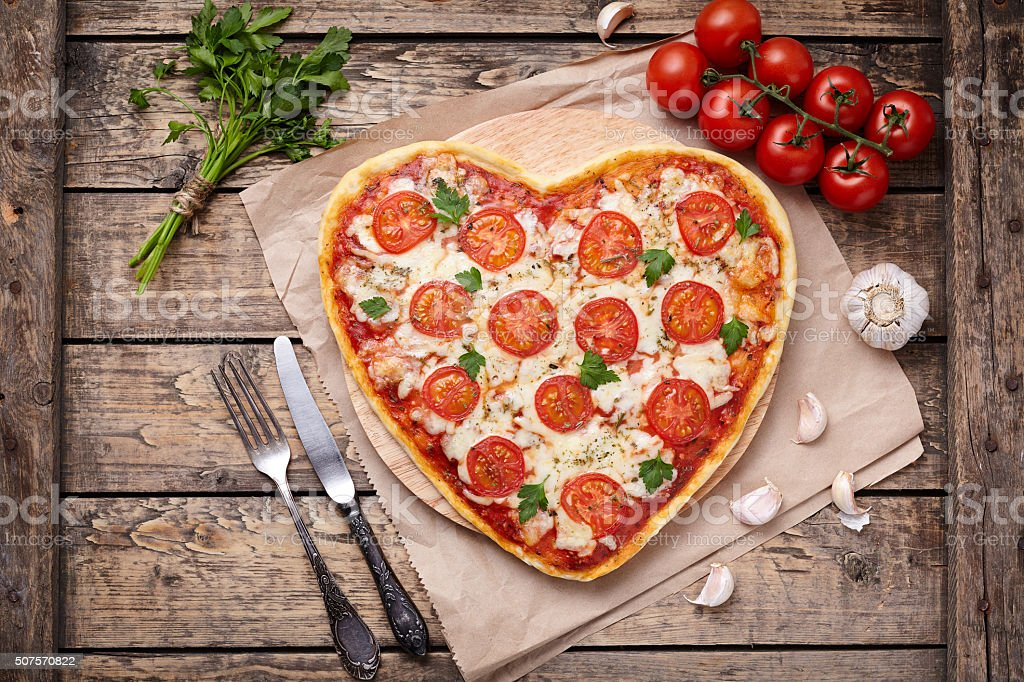 Heart shaped pizza margherita vegetarian love concept with mozzarella, tomatoes stock photo