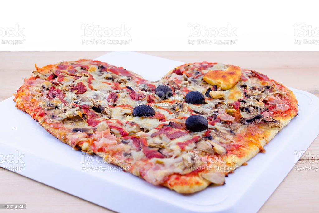 Heart shaped pizza on table royalty-free stock photo