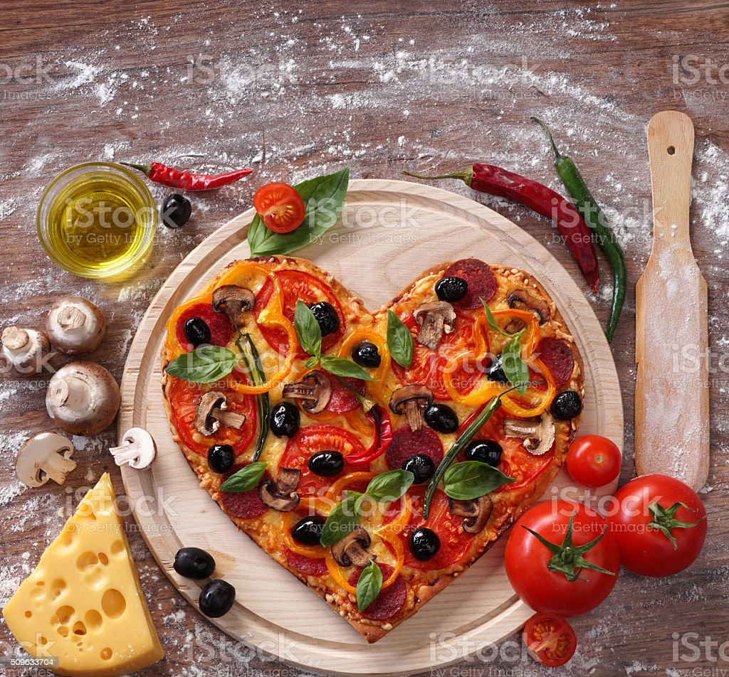 Heart shaped pizza served on wooden table, closeup. stock photo