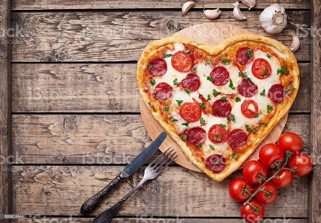 Heart shaped pizza with pepperoni, tomatoes and mozzarella on vintage stock photo