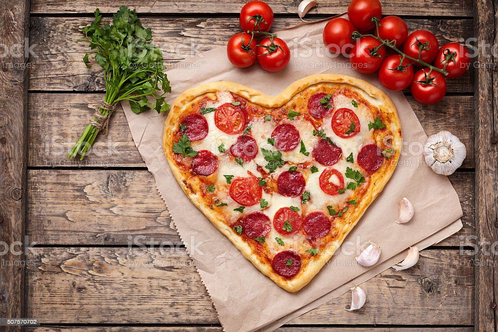 Heart shaped pizza with pepperoni, tomatoes, mozzarella, garlic and parsley stock photo