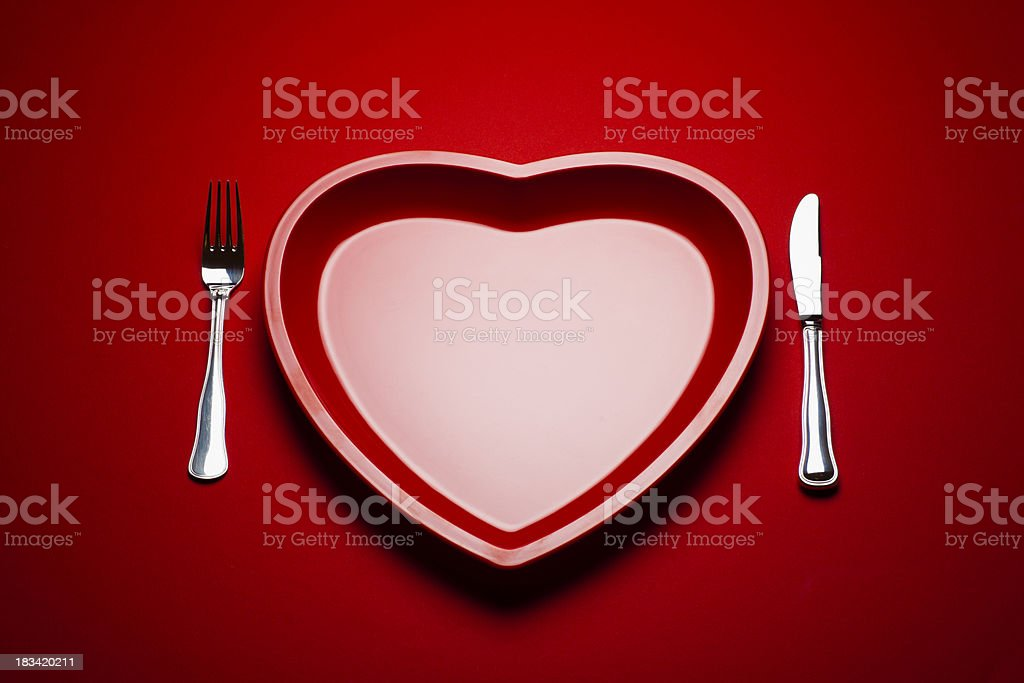 Heart shaped plastic plate on red background royalty-free stock photo
