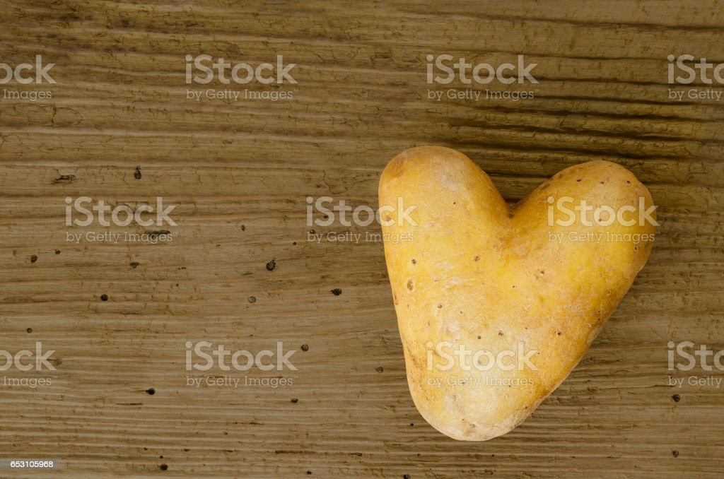 Heart shaped potato on old spruce wood board stock photo