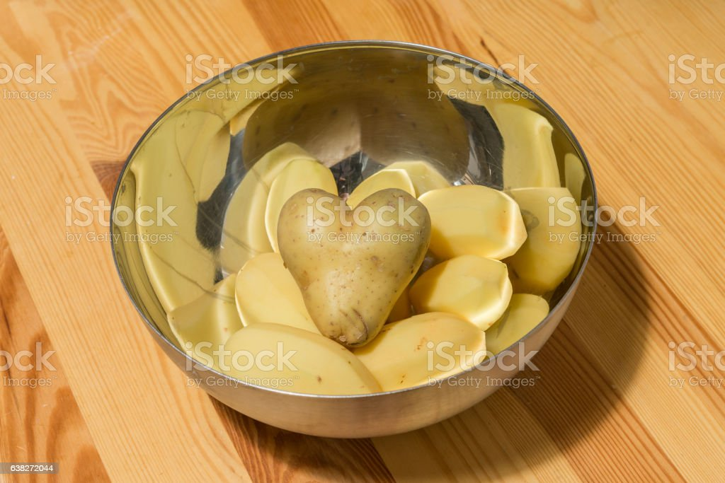 Heart shaped potatoes with other potatos in a bowl stock photo