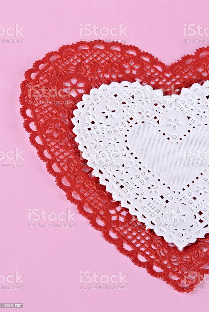 heart shaped red and white doilies on pink paper background royalty-free stock photo