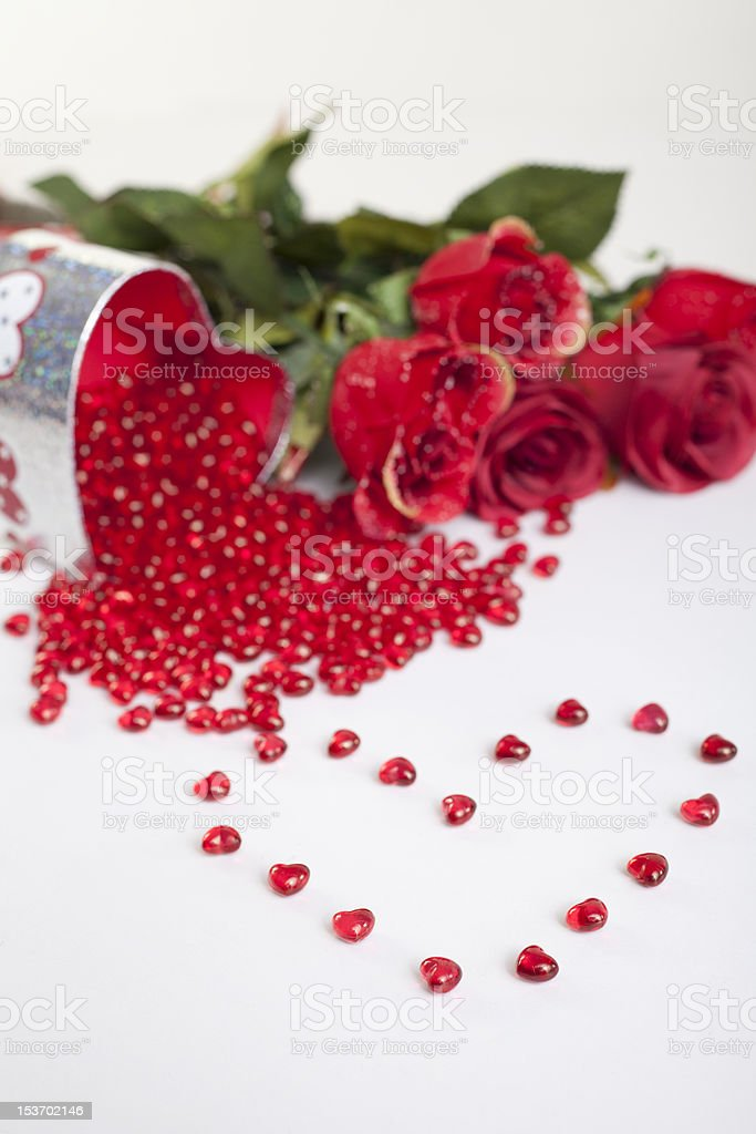 Heart shaped red gems with gift box and roses behind royalty-free stock photo