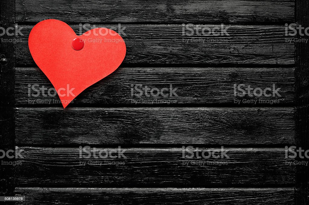 Heart shaped red note nailed to black wooden board stock photo