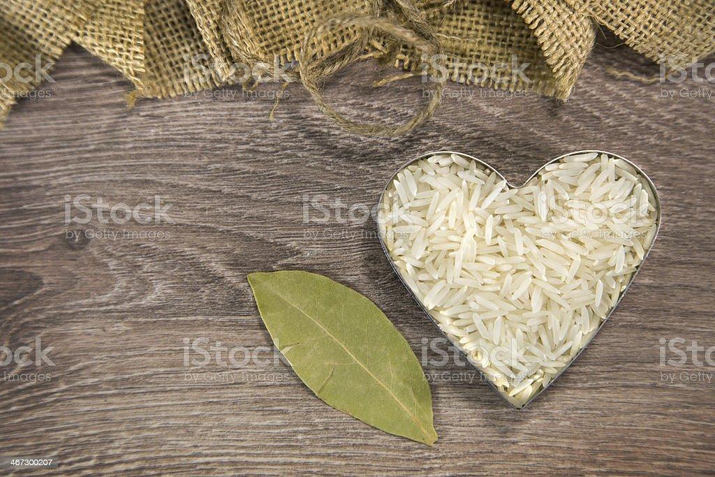 Heart shaped rice on wood background royalty-free stock photo