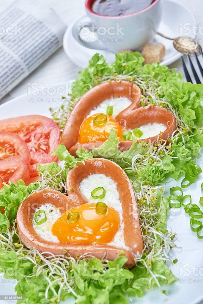 Heart shaped sausages with fried eggs stock photo