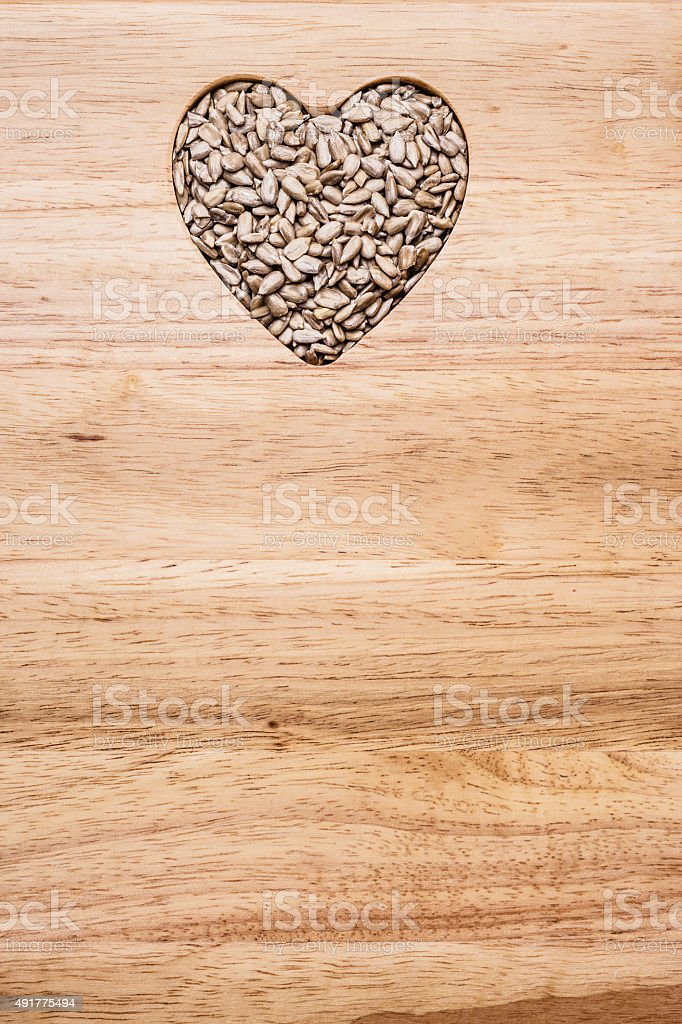 Heart shaped sunflower seeds on wood surface stock photo