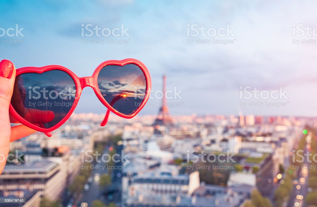 Heart shaped sunglasses and skyline of Paris during sunset (France) stock photo