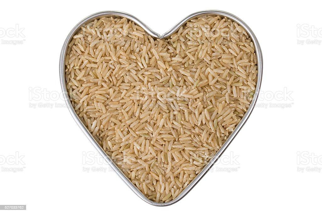 Heart shaped tin pan of half polished Brown Jasmine rice stock photo