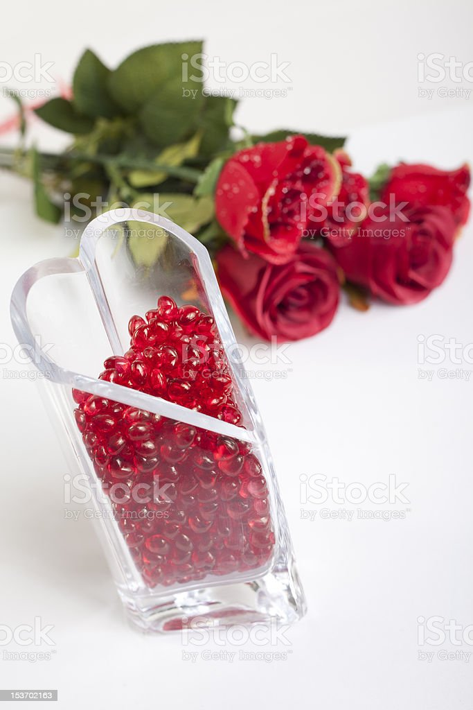 Heart shaped vase filled with red gems and roses royalty-free stock photo