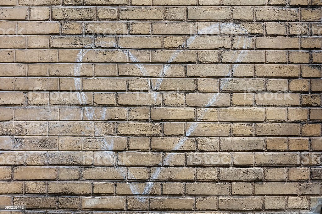 Heart sign drawn by white chalk on brick wall royalty-free stock photo