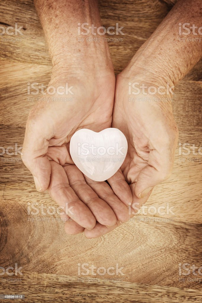 Heart Stone in Mature Hands on Wood Background stock photo