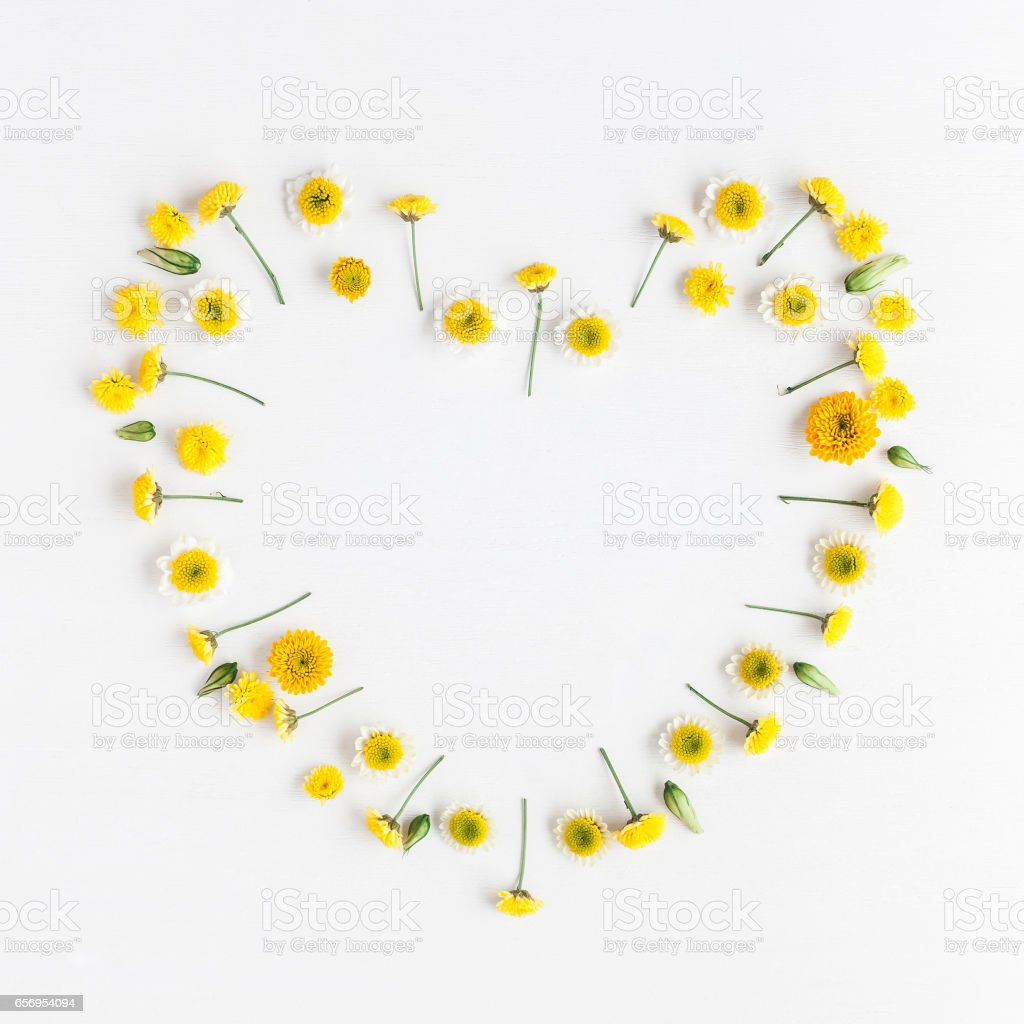 Heart symbol made of various yellow flowers. Flat lay stock photo
