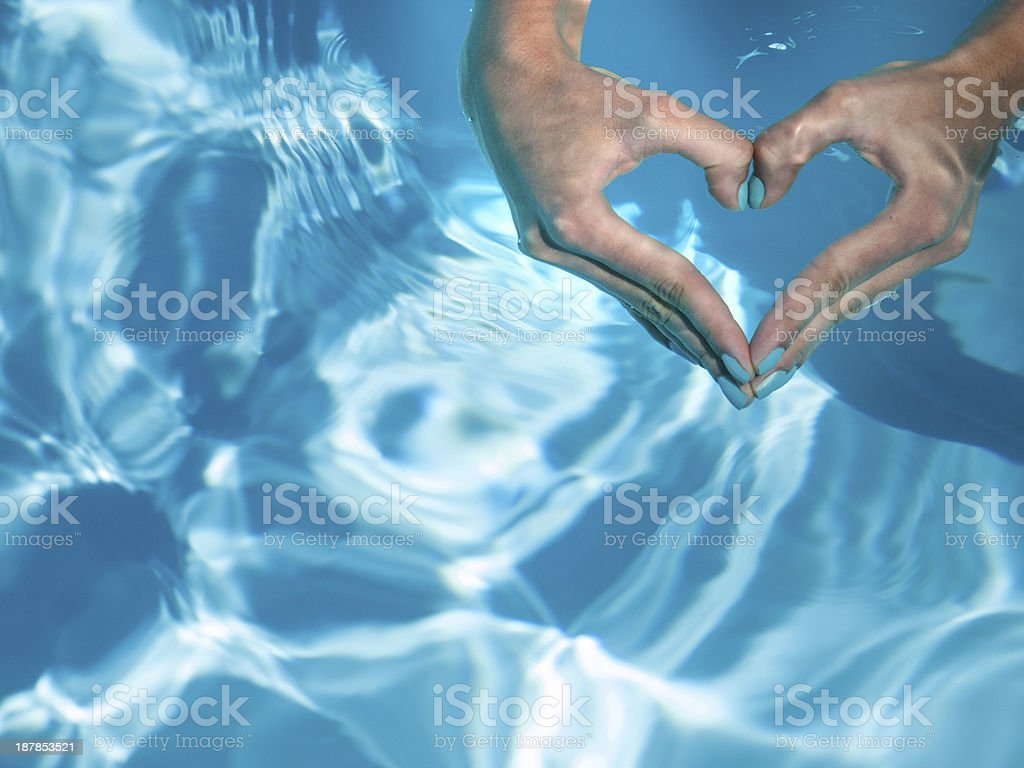 heart with hands in turquoise water stock photo