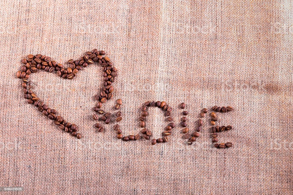 Heart with roasted coffee beans on the burlap background stock photo