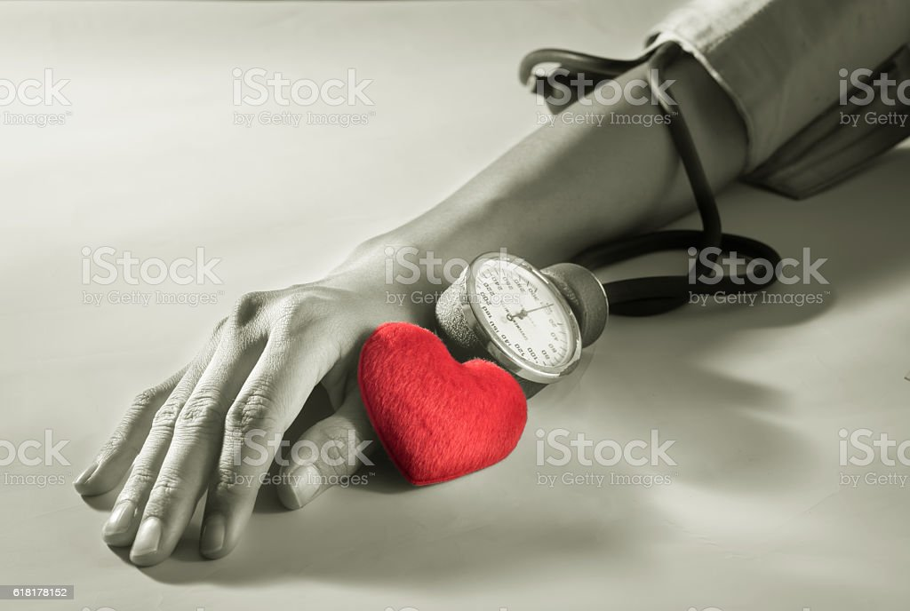 Heart with woman arm checking blood pressure. stock photo
