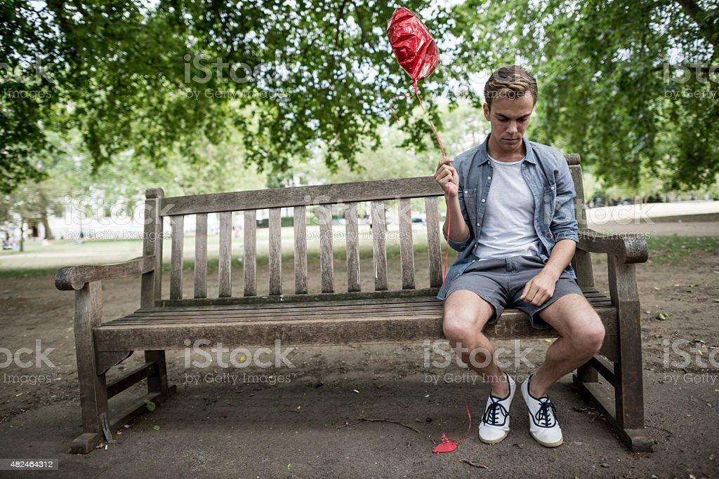 Heartbroken man at the park looking very sad stock photo
