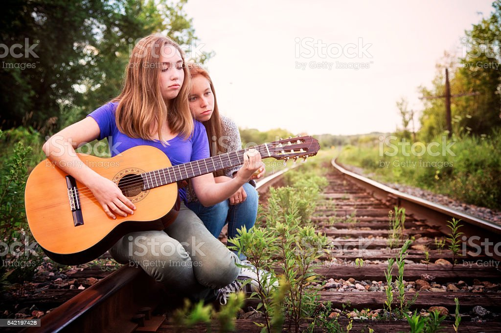 Heartbroken teenager plays sad song to friend on guitar stock photo
