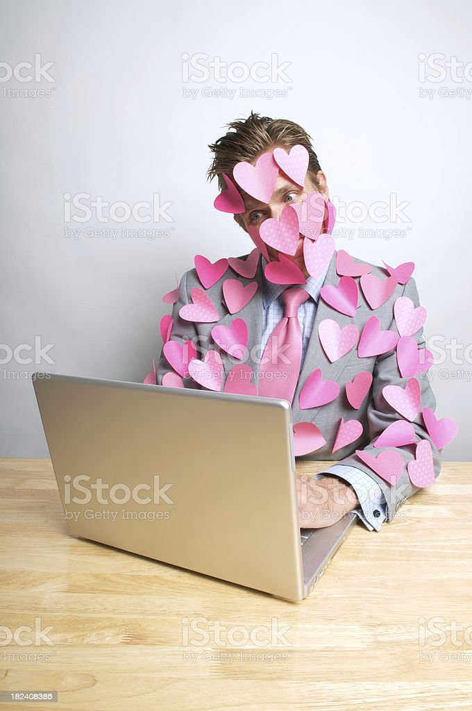 Heart-Covered Romantic Man Looking at Computer w Wide Eyes stock photo
