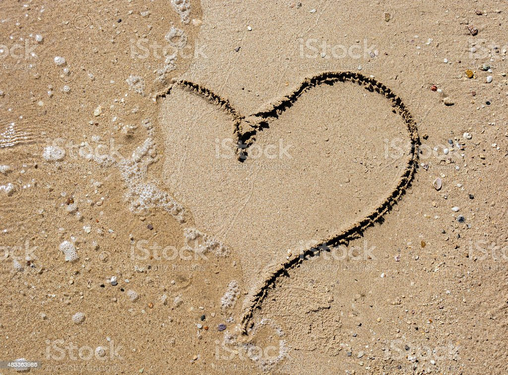 Hearth symbol on the sand beach on a sunny day stock photo