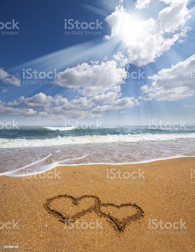 hearts drawn on the sand of a beach stock photo