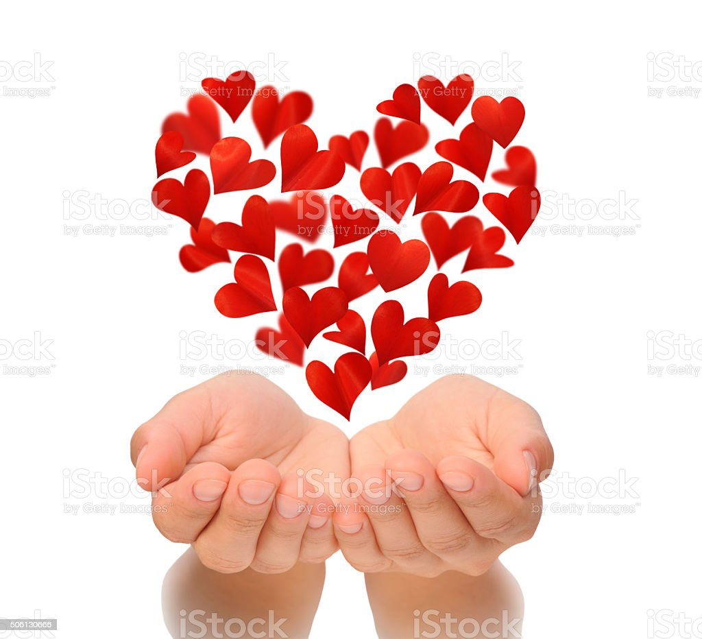 Hearts in heart shape flying over cupped hands of woman stock photo