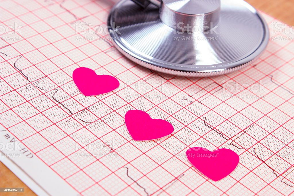 Hearts of paper and stethoscope on electrocardiogram graph stock photo