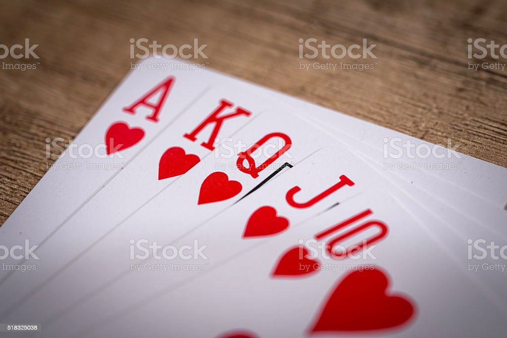 Hearts suit playing cards on wooden desk stock photo