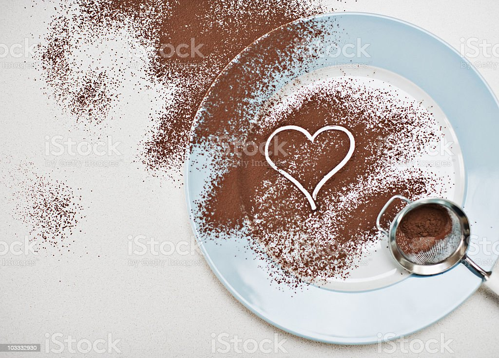 Heart-shape drawn into cocoa powder on plate stock photo