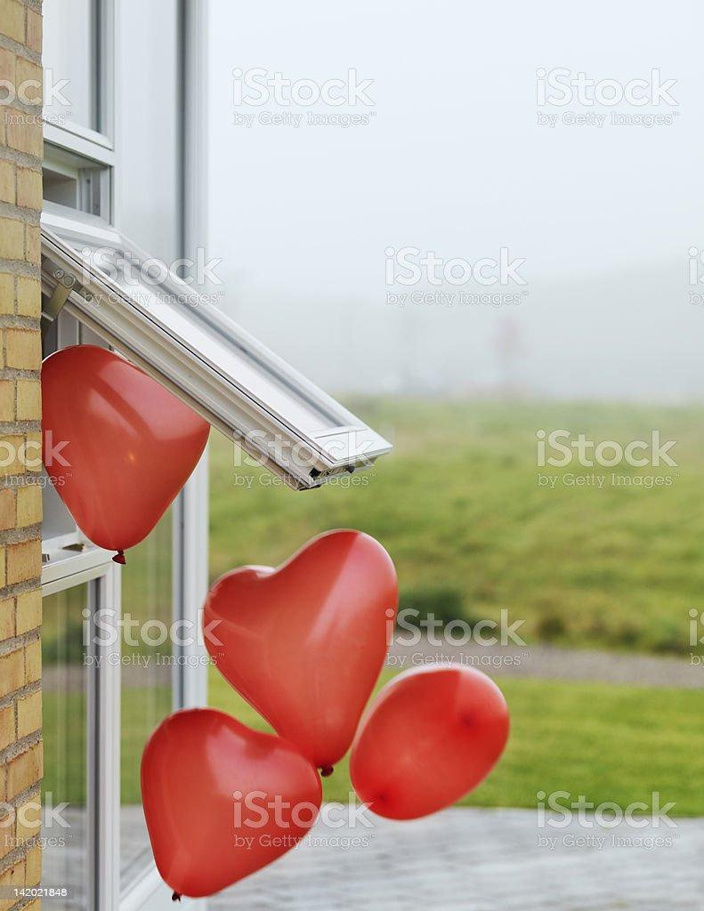 Heart-shaped balloons outside window stock photo