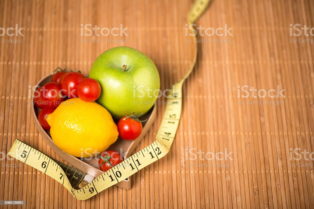 Heartshaped box with fruit and vegetables, exercise, healthy diet concept stock photo