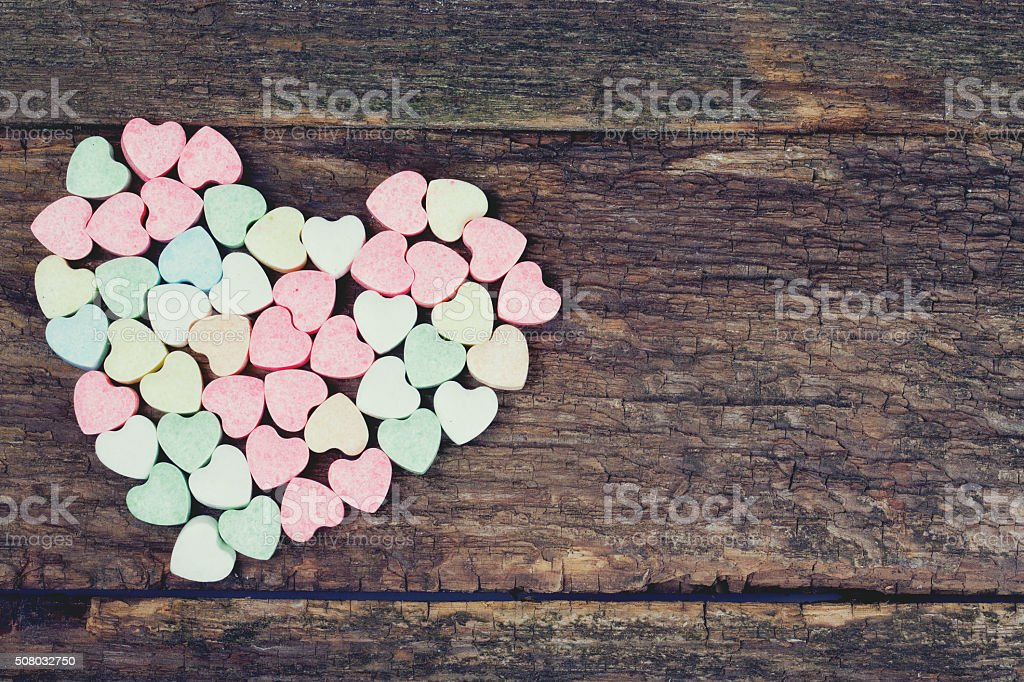 heart-shaped candies on wooden surface stock photo