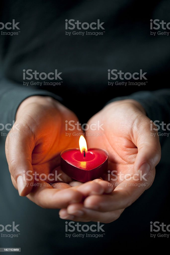 Heart-shaped candle in her hands royalty-free stock photo