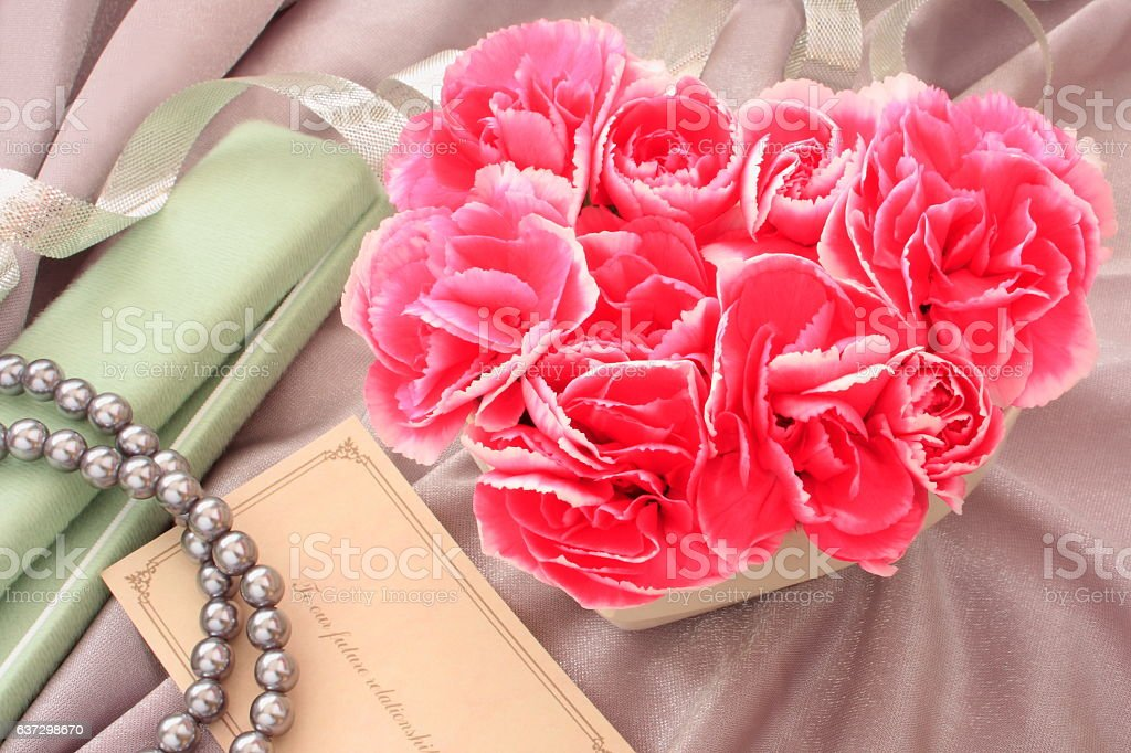 Heart-shaped flower arrangement of Carnation and jewelry gift stock photo