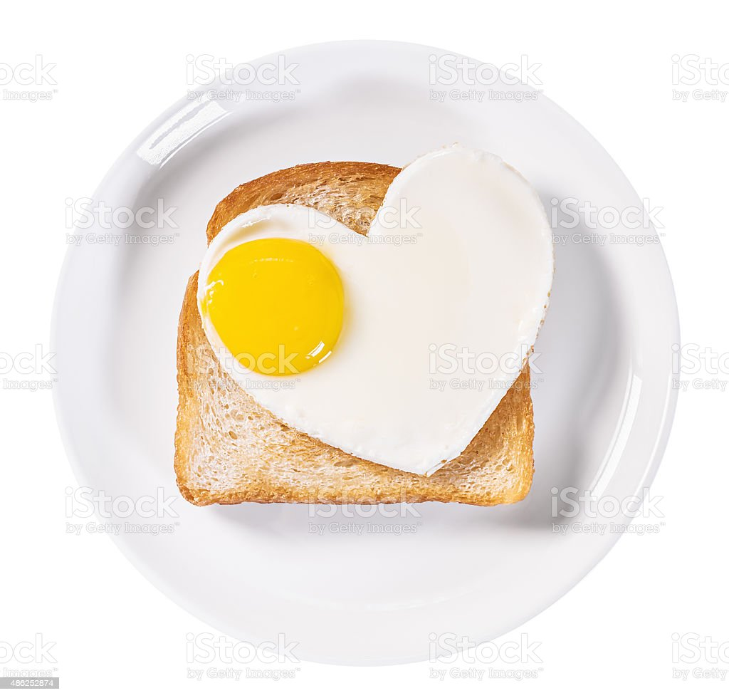 heart-shaped fried eggs and fried toast isolated stock photo