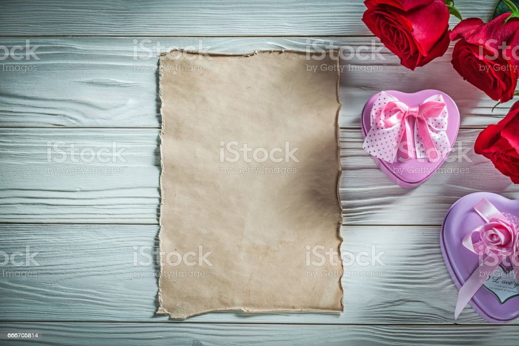 Heart-shaped metal present boxes red roses vintage paper on wood stock photo