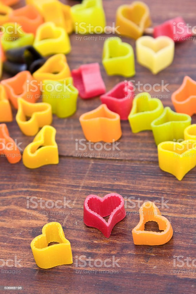 Heart-shaped pasta on wood table stock photo