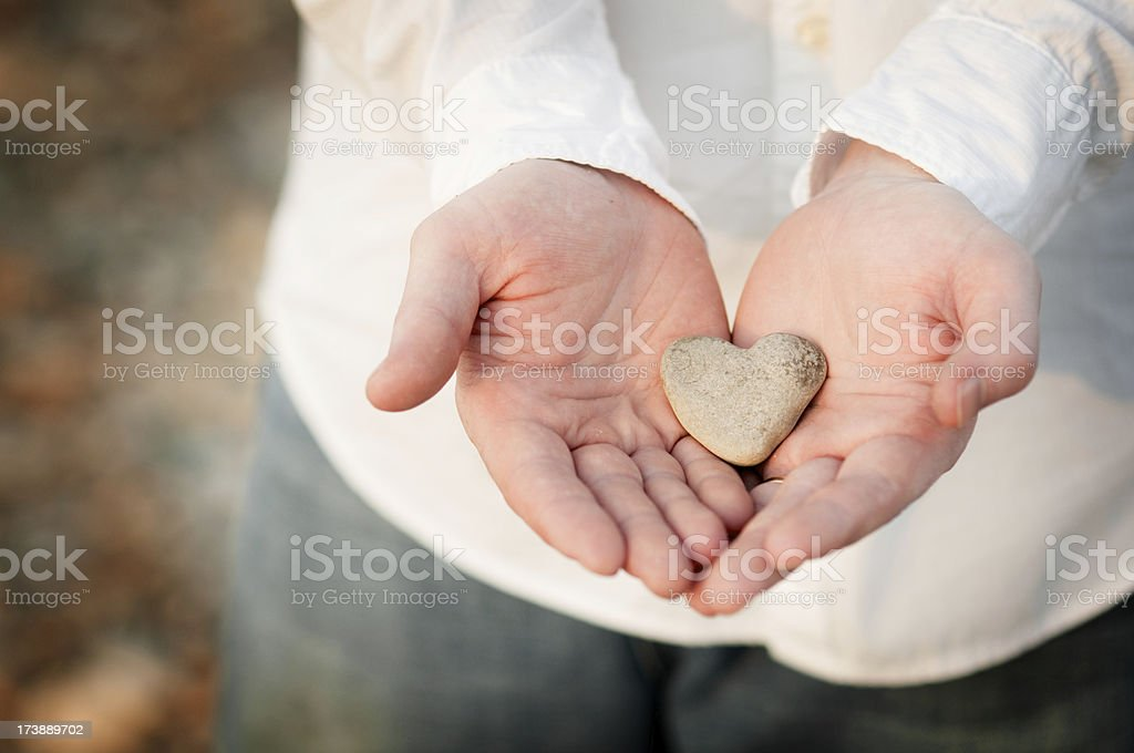 Heart-Shaped Rock in a Man's Hands stock photo