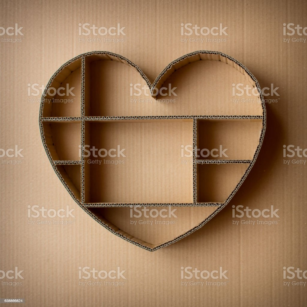 Heart-shaped shadow box hand-made of corrugated on cardboard background stock photo