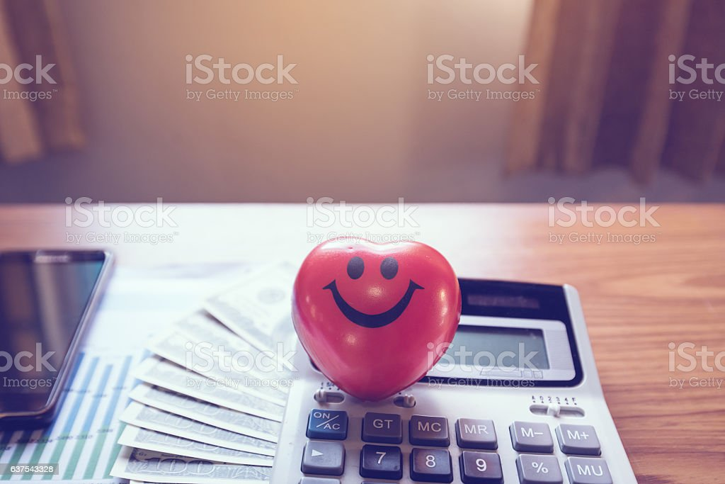 Heart-shaped smiley with money, calculator, mobile stock photo