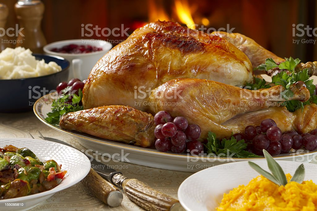 Hearty and cozy turkey dinner with fireplace in background royalty-free stock photo
