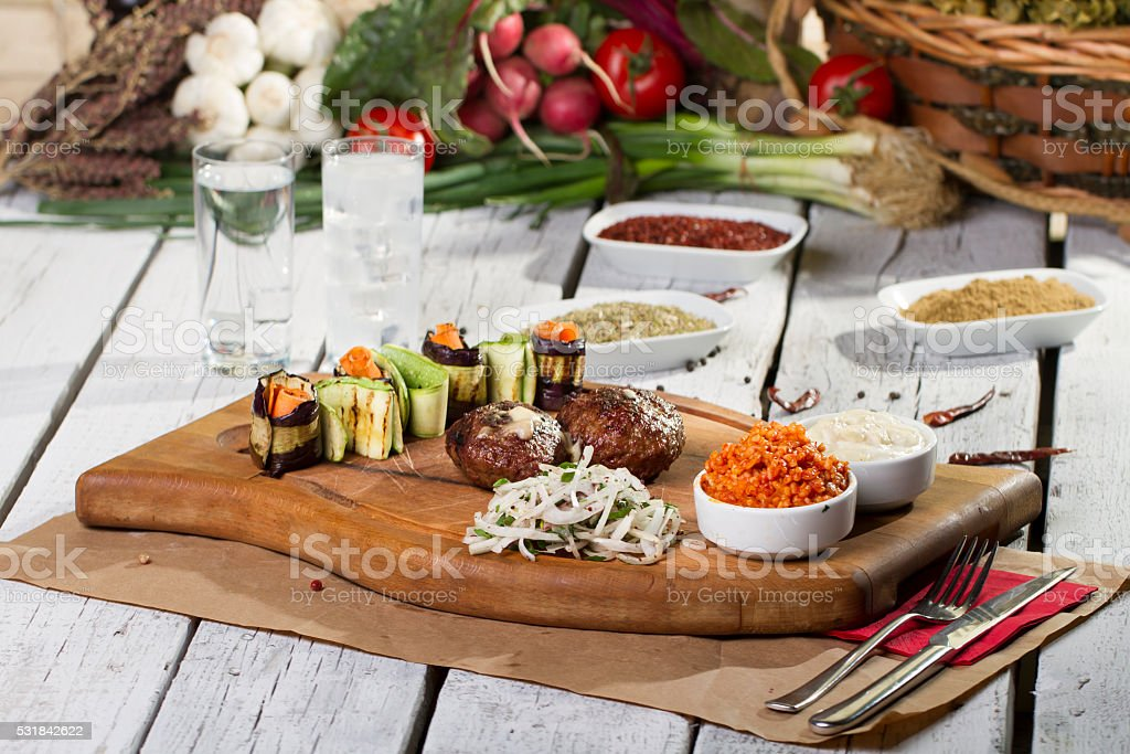 hearty meatballs served on wooden plate with onion and bulgur stock photo