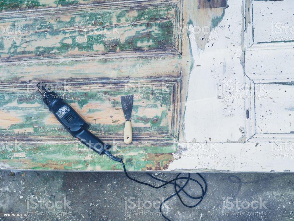 Heat gun and scraper on old door stock photo