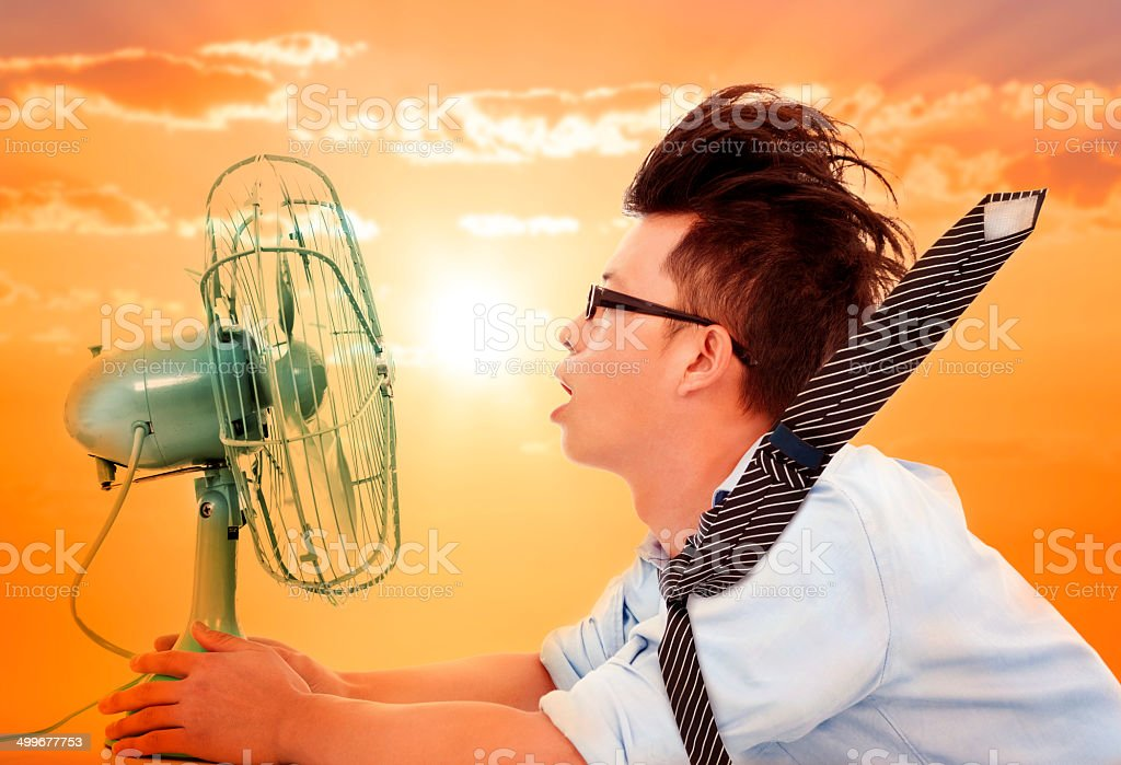 heat wave coming,business man holding a  electric fan stock photo