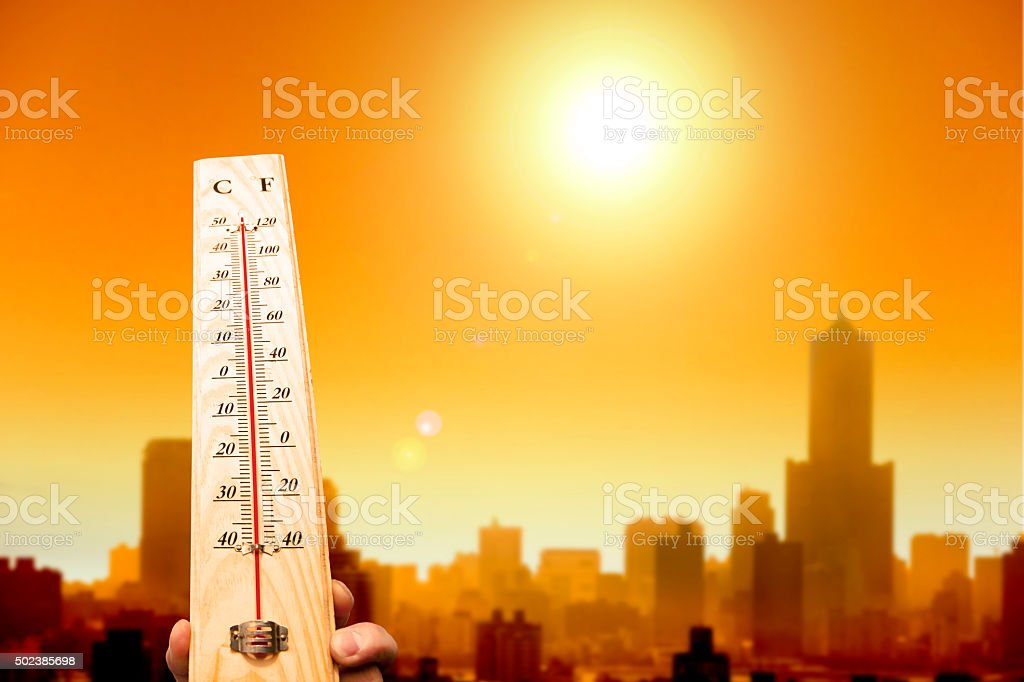 heat wave in the city and hand showing thermometer stock photo