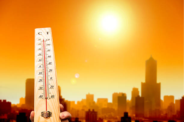 heat wave in the city and hand showing thermometer stock photo - Heat Temperature Pictures, Images And Stock Photos - IStock